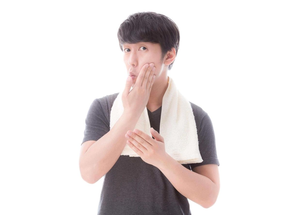 手で顔を触る男性